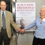 Dr. Jack Minker and Sophie Cook with the cover of Scientific Freedom & Human Rights